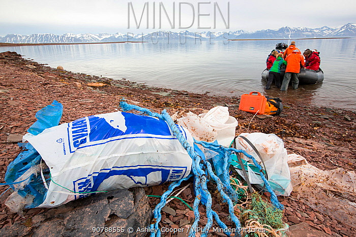 Tourists collecting plastic rubbish on a remote beach in Northern Svalbard, only about 600 miles from the North Pole. The plastic has been washed ashore by ocean currents. July 2013