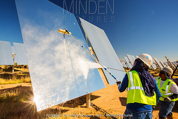 Workers washing the heliostats to maximise reflective power at the Ivanpah Solar Thermal Power Plant,  the largest solar thermal plant in the world. It covers 4,000 acres of desert and produce 392 megawatts (MW) of electricity. Mojave Desert, California, USA. September 2014.