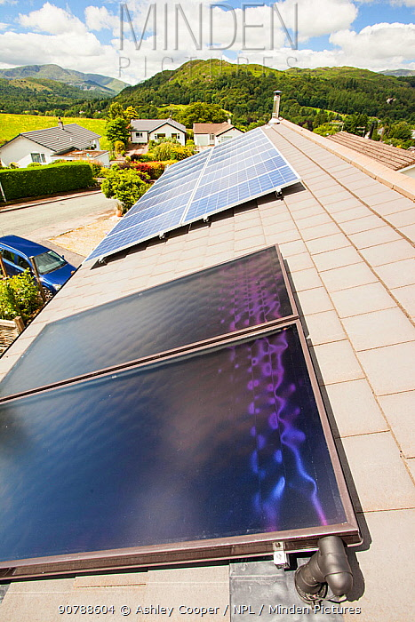 Solar thermal panels for heating hot water with solar PV electric panels behind on a house roof in Ambleside, Lake District, UK. July 2012