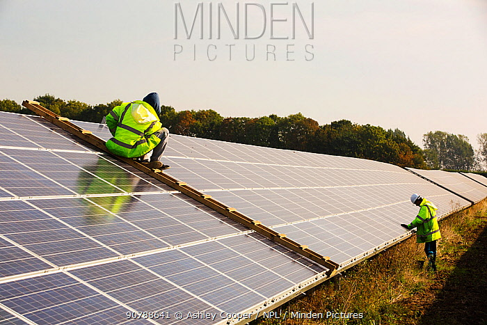 Technicians work on Wymeswold Solar Farm the largest solar farm in the UK at 34 MWp, based on an old disused second world war airfield, Leicestershire, UK. It contains 130,000 panels and covers 150 acres. September 2013
