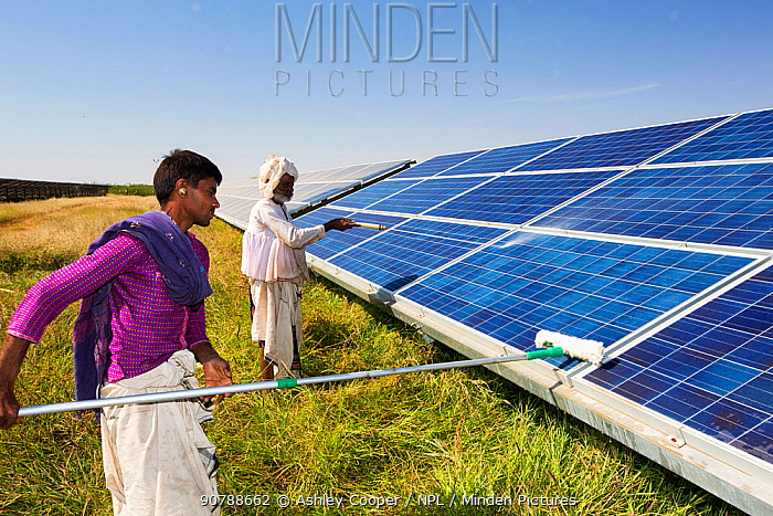 Asia's largest solar popwer station, the Gujarat Solar Park, in Gujarat, India. It has an installed capacity of 1000 MW. Here workers wash dust off the panels to increase their efficiency. December 2013
