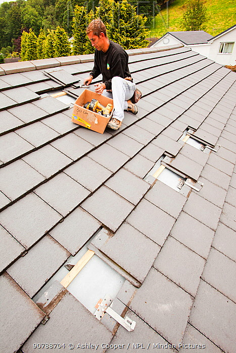 A techinician fitting roof brackets to a house roof in Ambleside, Cumbria, UK, to support solar photo voltaic panels. August 2011