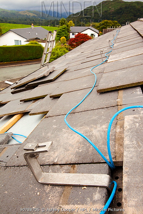 Fitting wiring to a house roof in Ambleside, Cumbria, UK, to support solar photo voltaic panels. August 2011