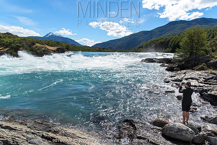 Woman taking picture of Baker River, Patagonia, Chile, January 2017.