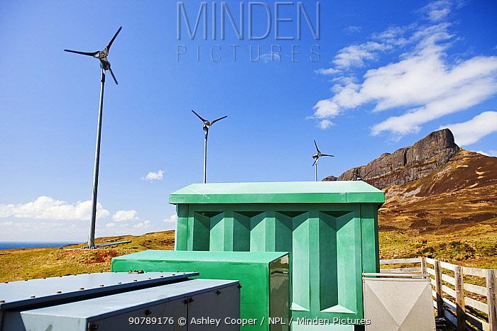 Four wind turbines beneath An Sgurr, Isle of Eigg. Isle of Eigg produces all the energy the island nees from renewable energy. Eigg, Scotland, UK, May.