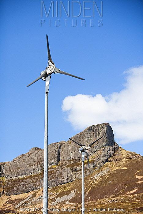 Wind turbines beneath An Sgurr, Isle of Eigg. Isle of Eigg produces all the energy the island nees from renewable energy. Eigg, Scotland, UK, May.