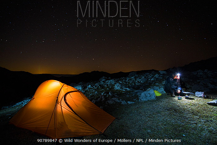 Hiker heating up water beside his tent under starry sky over a rocky limestone ridge in Mehedinti Plateau Geopark, Romania, October 2012