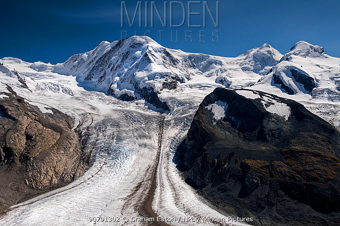 The Gorner Glacier with the Briethorn in cloud, Valais, Switzerland. September 2017. The glacier has a medial moraine running along its centre, formed when two glaciers with lateral moraines merge.