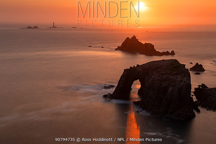 Sunset through Enys Dodnan Arch, with the Armed Knight rock and Longships lighthouse in the distance, Land's End, Cornwall, UK. May 2018.