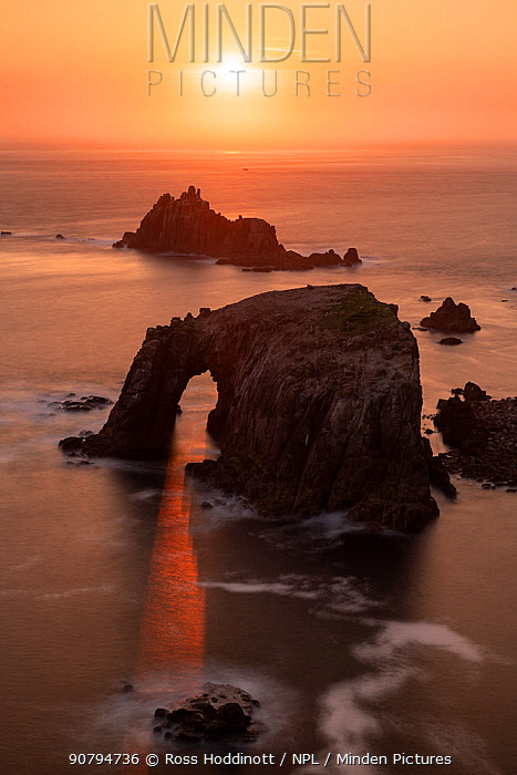 Sunset through Enys Dodnan Arch, with the Armed Knight rock in the distance, Land's End, Cornwall, UK. May 2018.