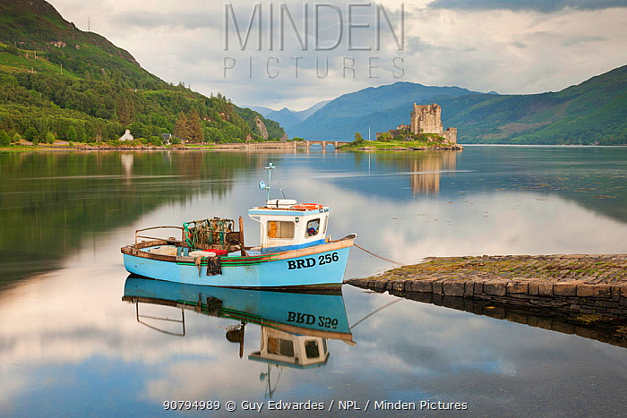 Boat in Loch Duich with Eilean Donan Castle in background, Highlands, Scotland, UK. July 2012.