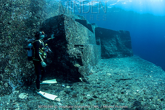Scuba diver exploring the Yonaguni Monument, a submerged rock formation off the coast of Japan. It is unknown if these sandstone rocks are formed naturally or are of human construction, Yoguni, Japan. 2017.