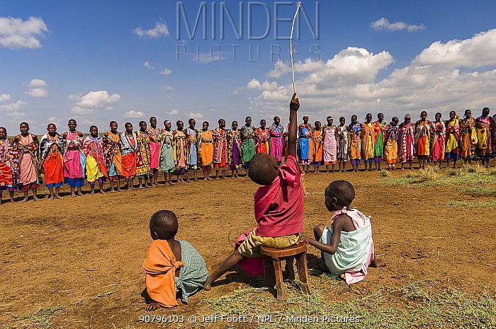 Maasai children watch woman singing traditional song, Maasai village, Kenya. September 2006.