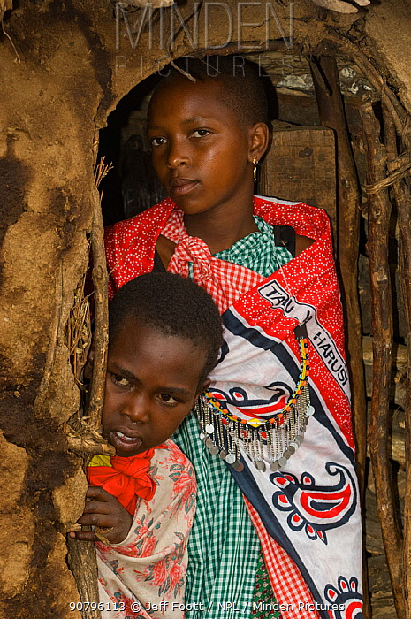 Maasai woman and child peering out hut, Maasai village, Kenya. September 2006.