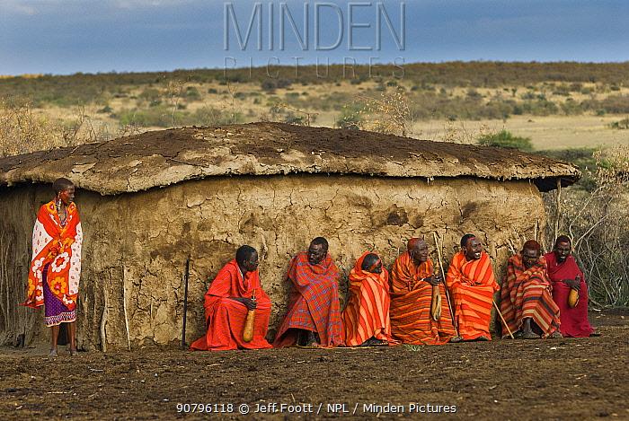 Maasai village elders with drinking gords and Maasai woman in front of hut, Maasai village, Kenya. September 2006.