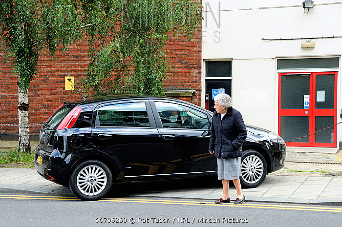 Elderly lady walks out into road as pavement is blocked by badly parked car, Holloway, London, England, UK, July 2009.