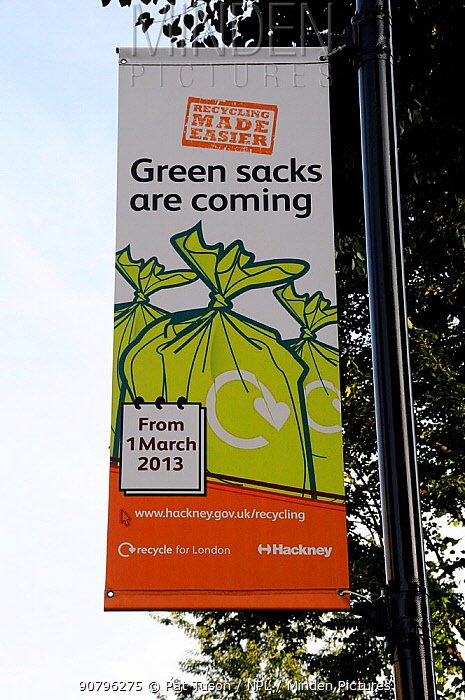 Banner saying 'Green sacks are coming' hanging from lamppost to encourage local residents to recycle their waste. The London Borough of Hackneys operates a mixed or commingled system of recycling, Hackney, London, UK, August 2013.