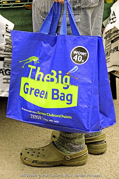 The big green bag, Tesco reusable shopping bag held by man, Islington Farmers Market, London, UK