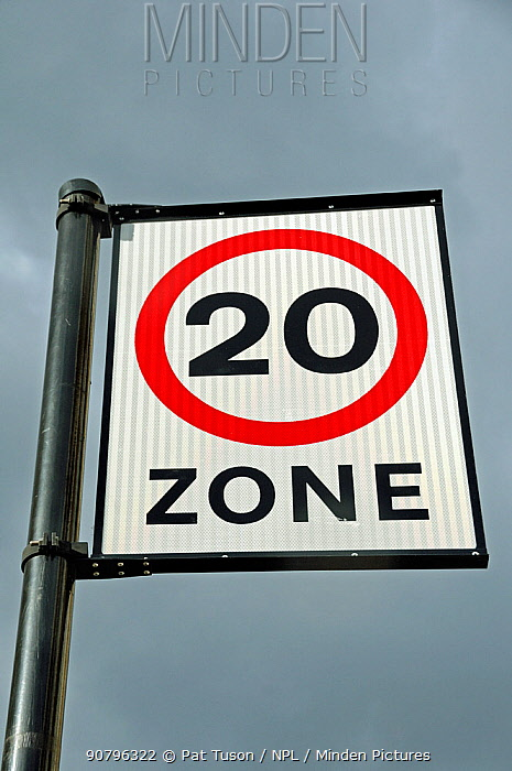 20 mph traffic speed limit zone sign against sky, London, UK
