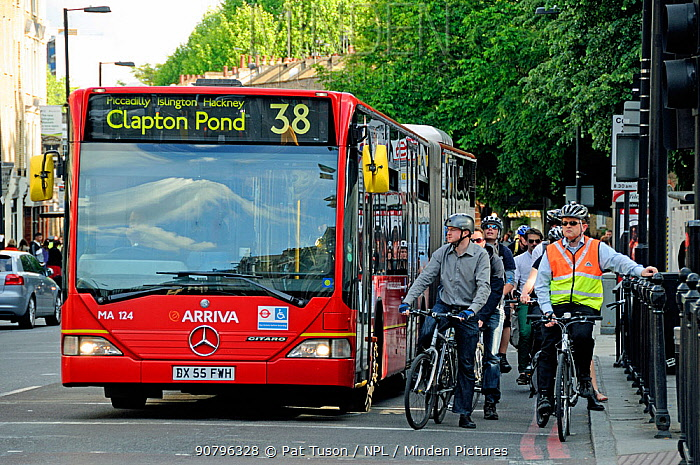 Bus and commuter cyclists waiting at traffic lights, Angel, London Borough of Islington, UK