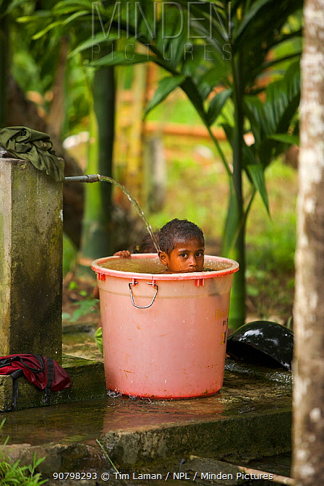 A child taking a bath in a large bucket. Waifoy Village, Waigeo Island, West Papua, Indonesia, April 2007