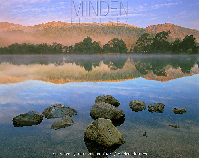 Misty reflection on Lake Coniston at dawn, Lake District, Cumbria, England.