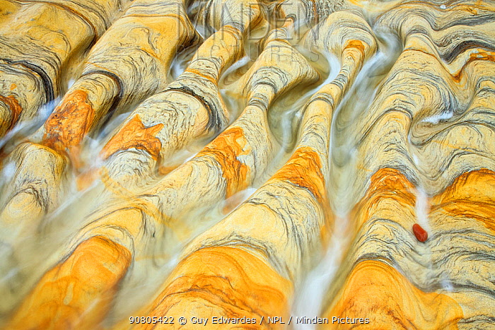 Water flowing over weathered rock with natural patterns, Northumberland Coast, England, UK.