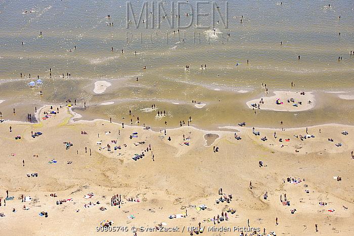 People on beach and in shallow sea. Parnu, the summer capital of Estonia. Parnumaa, Western Estonia. July 2010.