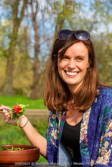 Woman enjoying a vegan picnic salad, North London, England, UK, March 2019. Model released.