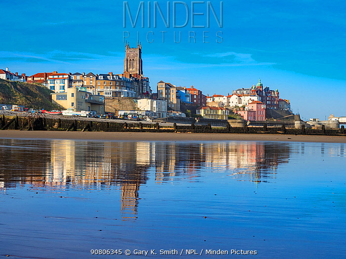 View of Cromer town with reflection on the wet sand. Norfolk, England, UK. October 2017.
