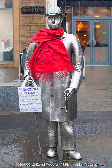 Statue with climate change protest sign. Extinction Rebellion action in Carmarthen, Wales, December 2018