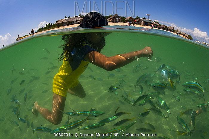 Filipino girl feeding fish off Snake Island in Honda Bay, Palawan.