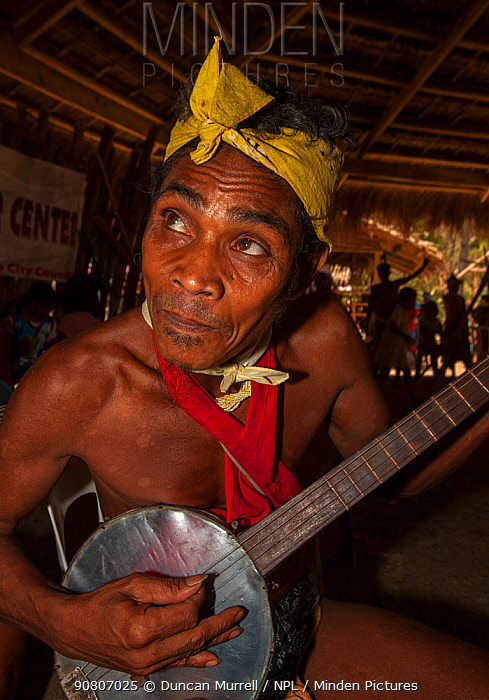 Man of the Batak indigenous tribe playing a stringed instrument in the Batak Visitors Centre at Barangay Concepcion, Puerto Princesa, Palawan, the Philippines.