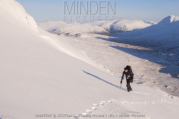 Winter hiker with ice axe climbing Beinn Fhada, Glen Affric, Kintail, Scotland, UK, February.