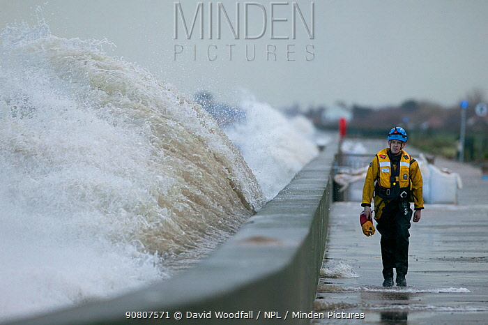 Waves crashing against the sea wall with a coast guard walking along it, Rhyl, Wales. January.