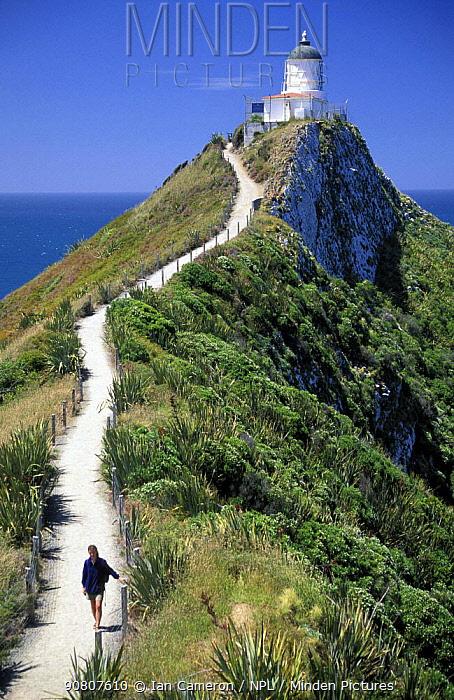 Woman on path near Nugget Point lighthouse, Curio Bay, South Island, New Zealand.