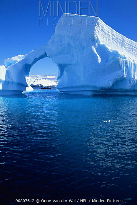 Expedition group in a RIB under a natural archway in a iceberg, Antarctic Peninsula.