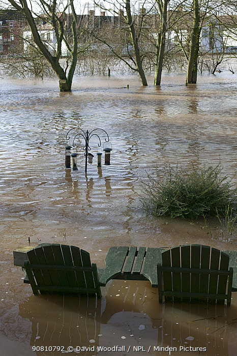 Garden table and chairs with bird feeders in flooded garden from February 2014 River Severn flood , Upton upon Severn, Worcestershire, England, UK