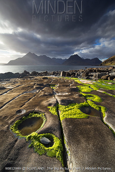 Rocky shoreline, Loch Scavaig and view to Cuillin mountians, Isle of Skye, Scotland, UK, April.