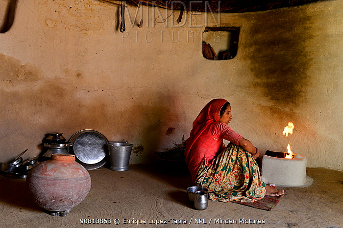 Woman preparing fire in her traditional house in a small village in Rajasthan, India. October 2018.
