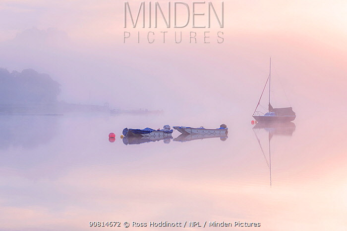 Sailing boat reflected in the mist at sunrise at Wimbleball Reservoir, Exmoor National Park, Somerset, UK. May 2017.