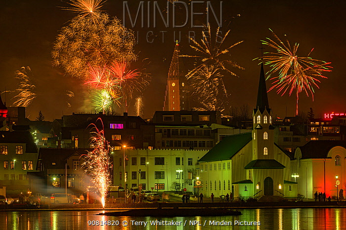 New Years Eve fireworks celebration in Reykjavik, Iceland with lights reflected in the water