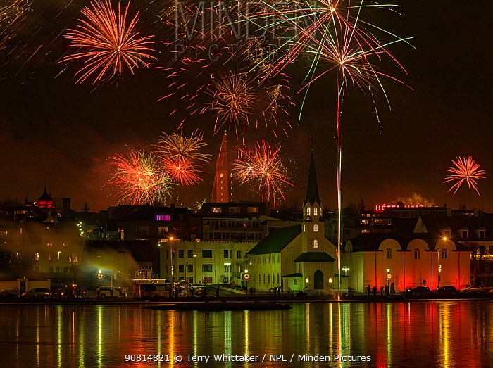 New Years Eve fireworks celebration in Reykjavik, Iceland, with lights reflected in the water