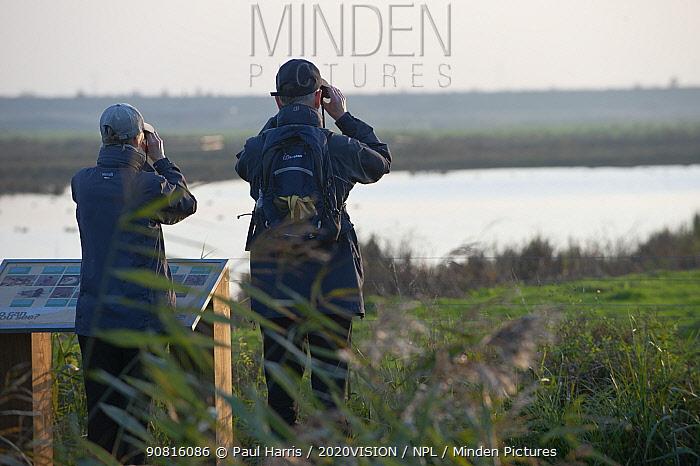 Two Birdwatchers looking over Rainham Marshes RSPB reserve, Essex, England, UK, November.