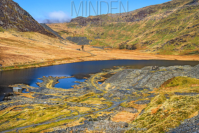 Looking east across Lake Cwmorthin showing the remains and spoil from the disused slate mine with Cnicht mountain covered in mist in the background, North Wales, UK, April 2018