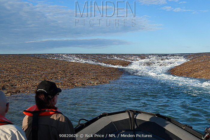 Tourists in boat watching water running off Montgomery Reef with ebbing tide. Doubtful Bay, The Kimberley, Western Australia. 2015.