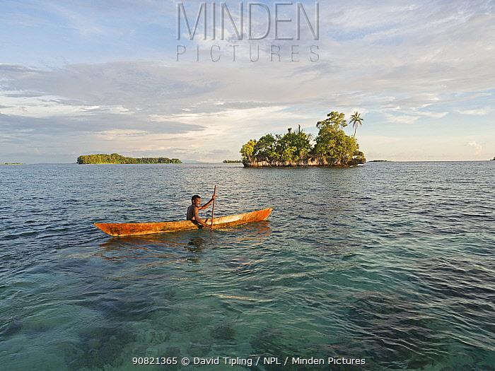 Fisherman in canoe in waters around New Georgia Islands, in evening light. Western Province, Solomon Islands. 2018.