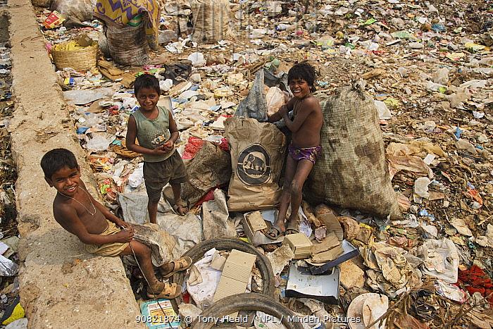 Three boys standing amongst rubbish, residents of landfill site. Guwahati, Assam, India. 2009.