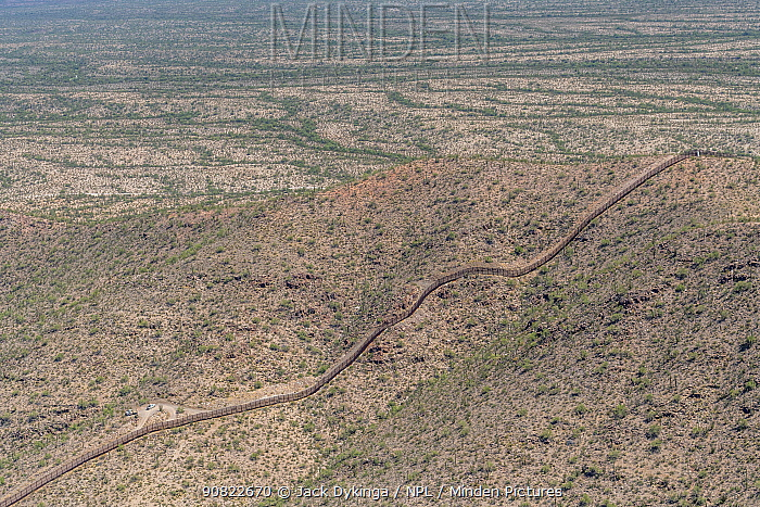 Aerial view of border Wall between Arizona, USA. and Sonora, Mexico, a ten foot high wall which will be replaced by Trump's thirty foot high barrier. The wall passes through the pristine Sonoran Desert landscape, Organ Pipe Cactus National Monument. September 2019. Aerial support by LightHawk.