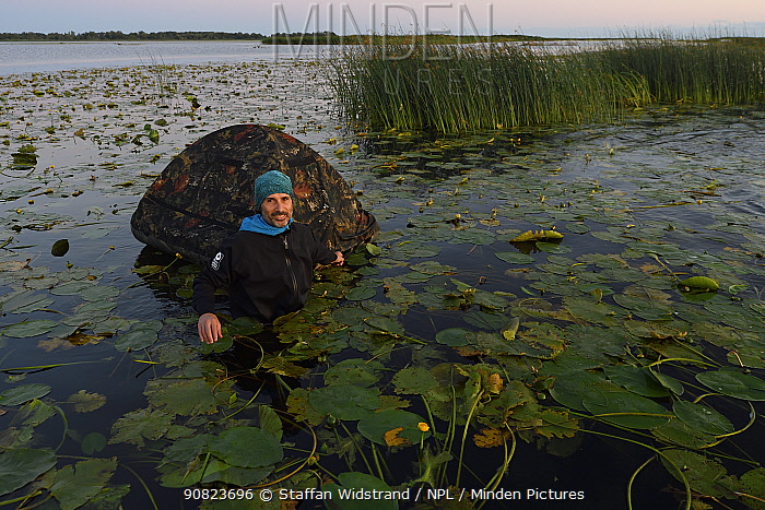 Phographer Oscar Dominguez in water with floating hide in the Nemunas Delta Nature Reserve, Lithuania.